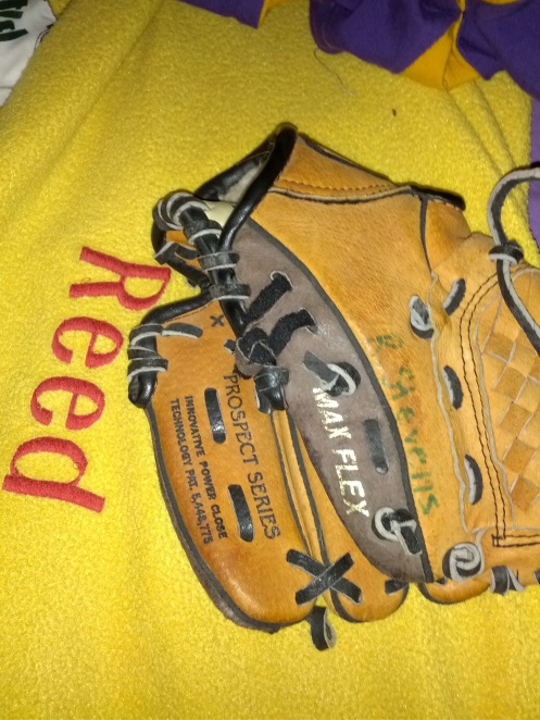 Reed's t-ball glove on his bed.